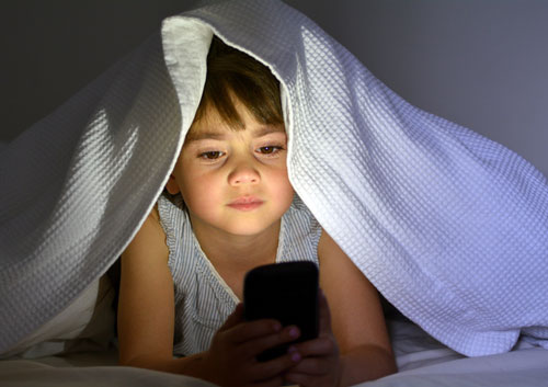 child with a smartphone preparing for sleep